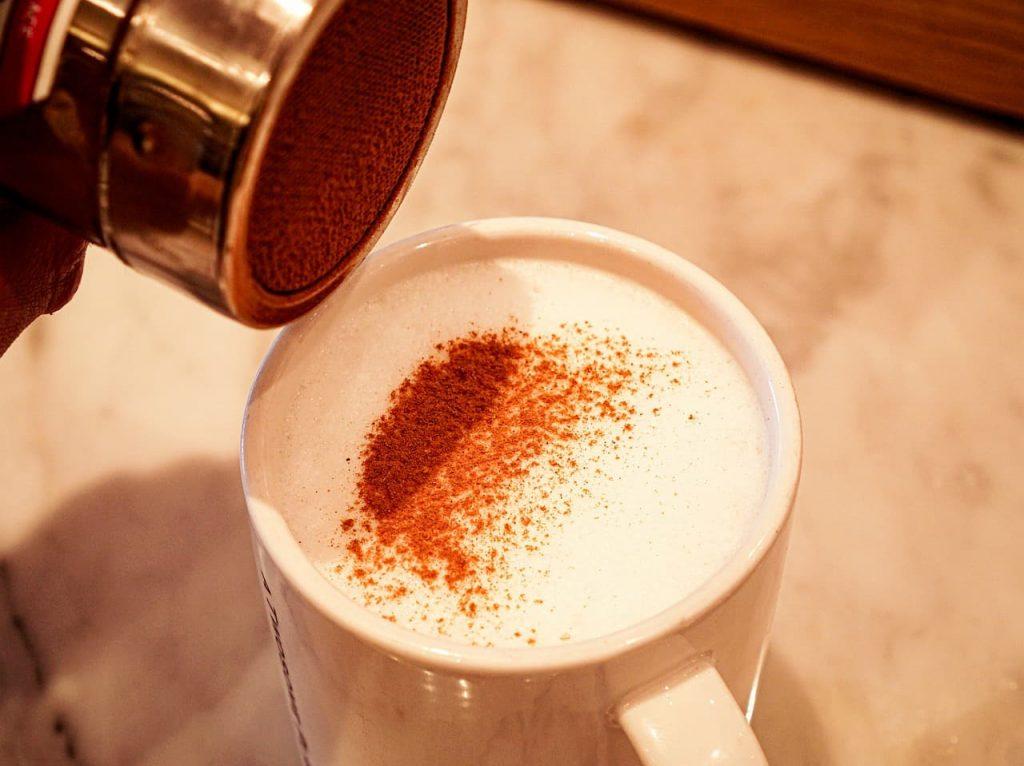 コーヒーにシナモンパウダーをかける